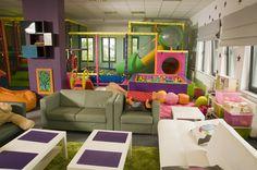 Prezentowane zdjęcie przedstawia wnętrze firmy Kids Play, które jest swoistym placem zabaw dla dzieci. Na pierwszym planie widoczny jest kącik dla rodziców, którzy mogą sobie usiąść, zrelaksować się czy odpocząć, natomiast na drugim planie widać - zjeżdżalnie, baseny z piłeczkami, tunele - miejsce zabawy dla dzieci.