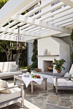 Elegant all-white outdoor living room with whitewashed wood furniture below the slatted pergola.