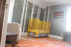 Woodland-themed nursery with a DIY yellow crib and bright accents - we're obsessed!