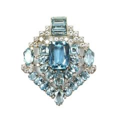 Art Deco aquamarine & diamond clip brooch by Cartier London, ca 1935, the stylized arrow of lozenge outline, centred by a principal rectangular cut aquamarine bordered by oval & fancy cut aquamarines in a geometric design, stepped diamond set detail above flanking a channel set arch of aquamarines.