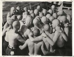 1943- Group of U.S. Coast Guardsmen, who have sworn to keep their heads shaved until they sink another submarine, huddle together on deck of a Coast Guard cutter.