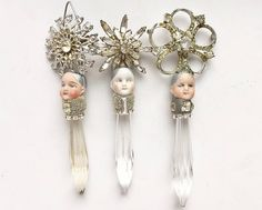 Please choose from those available in the drop-down menu. These lovely little pixies measure roughly 4 1/2 tal. I made them with antique chandelier crystal bases, rhinestone strands, micro silver beads, antique German bisque heads, and vintage rhinestone pins/clips. The fastening mechanisms are still present on the back of some. The heads are scuffed and faded (they had been buried outside a German doll factory for 100 years) but still have lovely expressions. Thank you for lookin...
