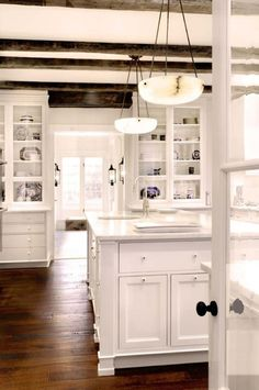 Crisp white kitchen with farmhouse details. Would love to have those exposed beams and hanging lights. georgianadesign: Architect Donald Lococo - DLa Design.