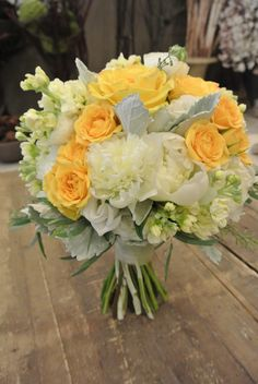 Bridal bouquet with roses, peonies, stocks, seeded eucalyptus and dusty miller. Designed by Forget-Me-Not flowers.