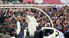 Pope Francis waved to tens of thousands of excited followers as he rode through the muddy streets on his Popemobile