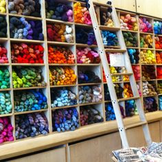 Happiness is the purl Soho yarn wall. Great idea to blend organizing yarn supplies and a book ladder!