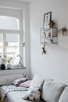 Cozy living room with beautiful windows, a small shelf and a grey couch with lots of pillows. Great Scandinavian inspired interior design.