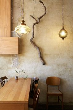 I love the texture of the plaster on the wall, the crispness of the wood, the twisted branch and the antique style glass lights all make me swoon.