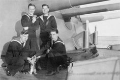"Sailors of HMS BELFAST with a young cat, possibly ""Frankenstein"", on the starboard side of A Turret."