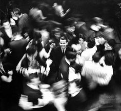 Dick Clark, standing in the middle of his teenage fans who are swirling around him on the studio dance floor during an episode of American Bandstand.
