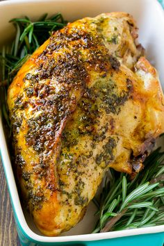 Garlic and herb roasted turkey breast in a baking dish with a rosemary garnish.