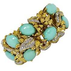 18K yellow gold bracelet tapering in width from 0.75 inches at the clasp up to 1.38 inches at the center. This Artfully crafted piece features 12 oval cabochon, robin's egg color, Persian turquoise measuring 16mm X 12mm. Interwoven in it's design are leaf motifs. There are assorted gold leaves, as well as leaves set with diamonds, for a total approximate diamond weight of 3.25ct.