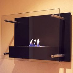 Radia Wall Mounted Fireplace. This sophisticated wall mounted fireplace features a chic, classic black frame and tempered glass face supported by stainless steel standoffs.