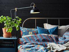 Un lit en métal noir, y compris le bleu à motifs avec ROSENRIPS Literie, VIGDIS taie bleu, RANARP Lampadaire / liseuse flowerpot noir et ingefära avec soucoupe Outdoor / terre cuite.