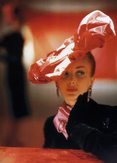 Awash in Pink  The images of Vogue legend John Rawlings often capture a certain cinematic quality. In this photograph, from the October 15, 1944, Vogue, a model wears an ambiguous but expressive look with her sculptural red and pink satin dinner hat by Suzanne et Roger and Helena Rubinstein lipstick.