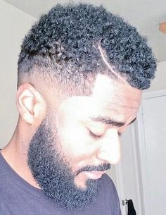 A photograph of a black guy with a curly hipster beard and a low fade haircut