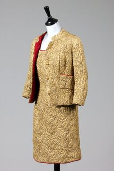 Vintage : Elizabeth Taylor's Chanel Cocktail Suit | Blouin Boutique  Kerry Taylor Auctions Passion for Fashion Sale  Elizabeth Taylor's Chanel couture gold brocatelle cocktail suit, circa 1964, un-labelled, comprising: simple A-line strapless cocktail dress, lined in raspberry silk, edged and piped with silk moiré grosgrain; the matching short, boxy jacket with stand collar, patch pockets, characteristic lion mask buttons.
