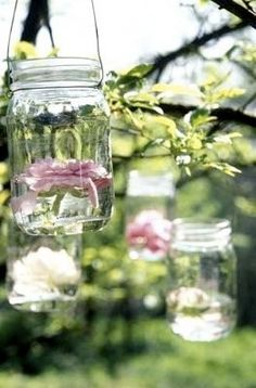 floating flowers or votive candles in mason jars hanging from tree branches