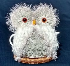 Owl Teapot Cozy made in a mix of wool, alpaca, and acrylic yarns. This one has the appearance of a baby owl, so cute. He has large amber eyes, soft white fluffy wings & back of acrylic baby wool, acrylic and wool blend grey & cream boucle lining in front body, white wool back body lining. Cream wooden nose. Cream colour fringing around eyes and wings. Fits a small to medium teapot, for 3-4 250 ml cup size pots Height of inside lining up to eyes 7 (18 cm), full height 9.5 (24 cm)…