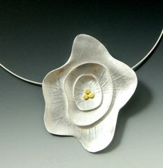 3 layers of sterling silver were used to create this pretty pendant. Each layer was handcrafted and textured to give life to the flower. 3 petite circles were then soldered to the middle. These circles are 22k bi-metal which is 22% gold fused to sterling silver plated and has much more gold content.