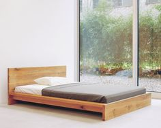 Designed by Philipp Manzier, 1999.The Mo bed is manufactured from solid wood 1 5/8 inch thick of either oak or walnut. The bed is available with two frame and headboard heights so as to provide easy entry and ideal comfort. In this version, the frame can house most available bed systems. There is a central bracket for additional strength, also enabling the use of two separate slatted frames. E15 offers slatted frames, which may be ordered separately. Available in Oak or Walnut.