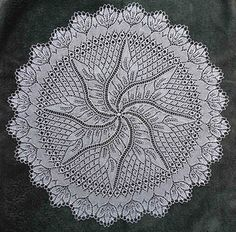 A round doily with spiral leaf motif center and leaf lace edging; worked in a fine crochet cotten thread.