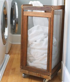Upcycling: Laundry hamper made from old framed window screens set atop three old planks with four casters attached to the bottom.