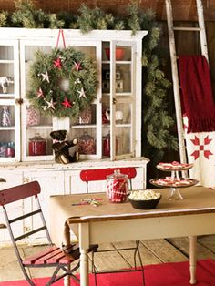 A wreath, greenery, a ladder with quilts, and red glassware give the feeling of a vintage Christmas