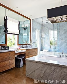 The spacious master bathroom includes a steam shower and freestanding bathtub in the center of the room. The ceiling light fixture is from Charles Edwards and the sconces are from Urban Electric.
