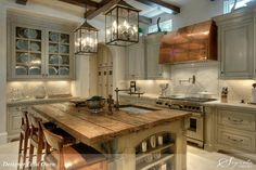 Adore these lighting fixtures.  Reclaimed wood countertop on island is nice and copper stove hood blends in well with the overall look.