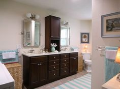 """Overall cost of bathroom, including gutting, new walls/ceiling, Congoleum floor tiles, tiled shower with ledge seat, Kohler toilet/faucets, StarMark cabinetry (cherry wood with Hazelnut stain), Vicostone quartz countertops in """"Taj Mahal"""", plumbing not moved:  $21,000. I have about $1,500 in the mirrors, towel racks, etc., from Rejuvenation.com. Sherwin Williams Steamed Milk walls, Cotton White trim.  Reversible Surya Newport rug:  http://www.rugs-direct.com/Details/details/118611/190128"""