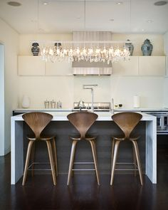 This strikingly contemporary kitchen features a sleek geometric design, with functional wooden stools, and a gorgeous modern crystal light fixture.