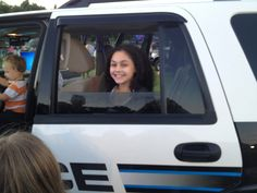 Carly happy in back of cruiser.