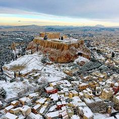 The Parthenon temple is seen atop of the snow-covered Acropolis hill in Athens, Greece. Snow closed schools in the capital, pressuring the government to speed up winter preparations for thousands of refugees living in camps around the country (AP)