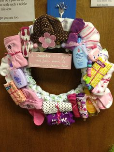 New twist-diaper wreath.  Used sturdy cardboard for the backing, attached diapers, wash clothes, Kleenex, socks, rattle, hats, burp rags with mini twist ties and ribbon.