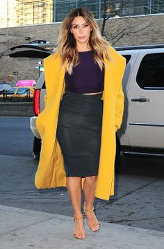 Kim Kardashian showed off her flawless off-duty style this week teaming a grey pencil skirt and purple crop top with a vibrant Max Mara coat.