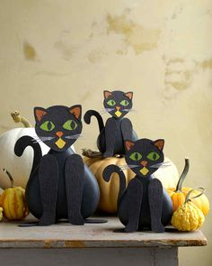 A family of black pressed-paper cats prowls through a pumpkin patch. Their bodies are made from different sizes of heart-shaped boxes turned upside down.
