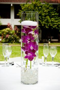 Floating candle atop orchids make for an easy #DIY centerpiece Wedding candles Ideas and Inspirations. Wedding candle displays