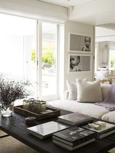 Beautiful Livng Room....gorgeous styling on the coffee table & Lovely Large Black & White photos of a child for wall decor