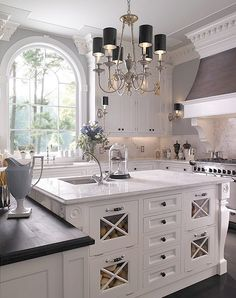 The island, range hood, millwork, wood top, chandelier and window make this kitchen incredible.