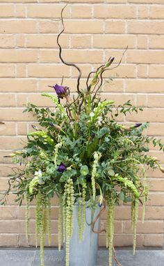 Lush foliage arrangement enhanced with chincherinchee and iris. #wedding
