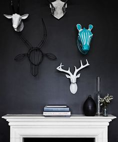 """Black painted walls add drama in the smaller front living room, allowing sculptural animal heads to """"pop"""".   Decorative **zebra** and **cow heads** from [Turner and Lane](http://www.turnerlane.com.au/?utm_campaign=supplier/