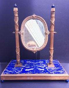 A Fine 19th Century French Bronze Dore and Real Lapis Lazuli Dressing Table Mirror    This magnificent example of French Empire Style with ormolu bronze Roman Fasces  Columns is mounted on a large rectangular base of beautiful, strong colored, real Lapis  Lazuli. It is surrounded with a gilded bronze band and standing on four Lapis Lazuli ball feet.  An oval shaped mirror framed in ornate bronze is hinged on the columns.  Large Lapis Lazuli beads surmount each column.     This outstanding…
