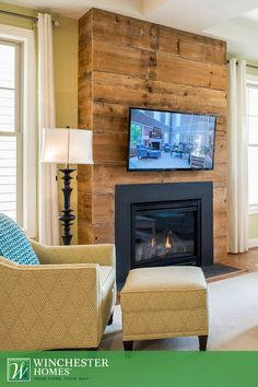 Rustic meets modern with the Chicago design's wood-covered fireplace. The warm, wood planks provide the perfect contrast for the black, contemporary fireplace surround. Without a mantel, this is the perfect place to install a wall-mounted television. #DreamHome