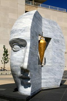 Carrara marble sculpture by Larry Kirkland in Denver, Colorado, depicting a  'Janus head' with a cast bronze & gold leaf plumb-bob (tool used in construction for finding a true vertical) dangling inside.