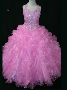 Beautiful Little Rosie Pageant Dress LR123. This organza pageant dress has a halter neckline, beaded bodice, and basque waistline. A ruffled ball gown skirt completes the look of this pageant dress. This adorable dress will make your little pageant girl a star.