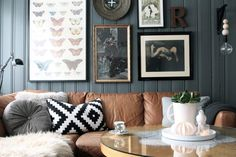 Tan leather couch with dark grey/blue wall, cushions & frames