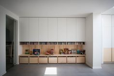 Wallcabinet with drawers on wheels for toys and visible CD storage, both in plywood.Storage room behind white doors.