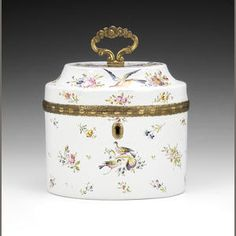 A fine English enamel tea caddy and inner cover, circa 1770. Birmingham or South Staffordshire, of oval form with fine quality gilt metal mounts and key escutcheon, the chamfered & hinged cover with gilt metal scrolled handle, the inner enamel cover with an acorn finial, painted with birds with brightly colored plumage, some in flight & others perched amongst flowers, including honeysuckle, iris & passionflower, further scattered sprays & sprigs around them, the interior lined with tinplate.