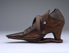 1625-1649 AD.- English. This is a rare example of a woman's slapshoe. Made of brown leather, the shoe has a long narrow toe with a flat end and a medium heel which stands on a leather extension of the sole. Its name derives from the slapping sound caused by the heel striking the extension of the sole while walking. The upper part of the shoe has extensions with eyelet holes in each side for laces, and the tongue has two pairs of eyelet holes. Found at Royal Ontario Museum.